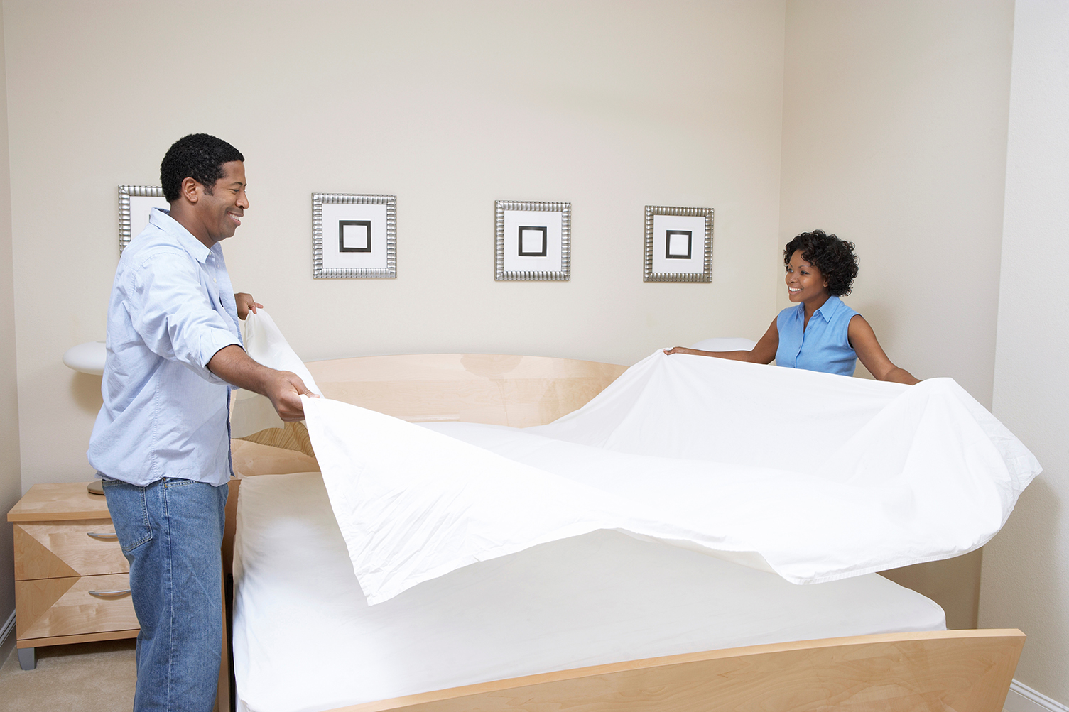 couple making bed with white flat sheet