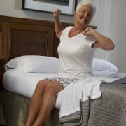 older woman stretches at the edge of her bed