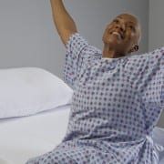 woman stretching happily on the edge of moisture wicking hospital bedding