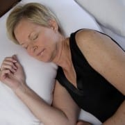 woman sleeping on her side in white moisture wicking sheets