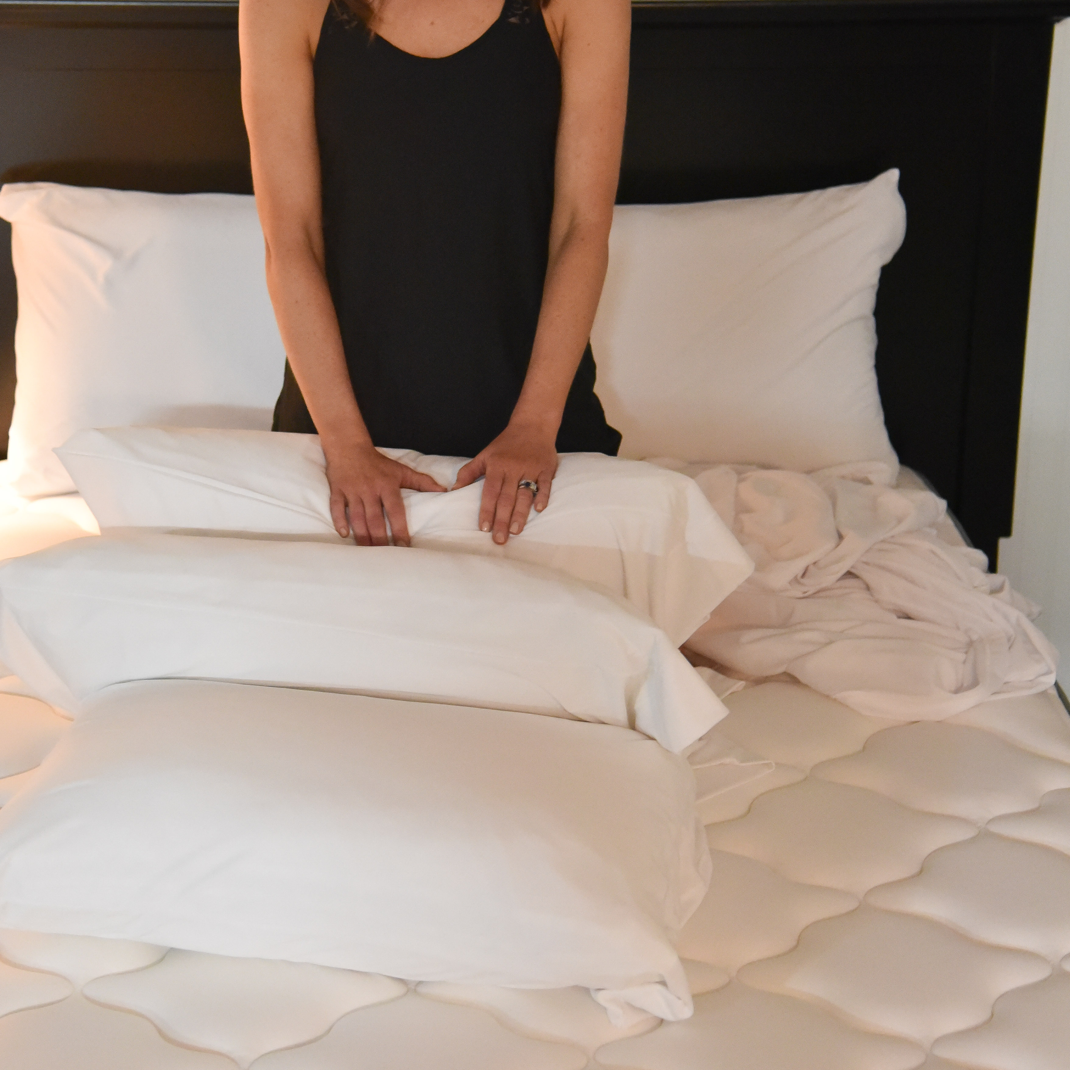 pillow case woman sitting up in bed surrounded by white pillows
