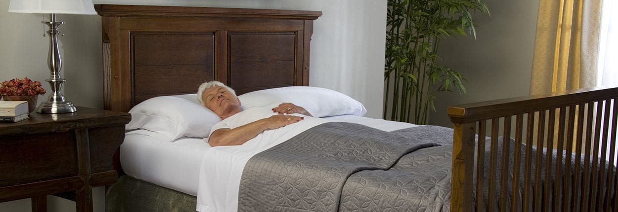 older woman laying in bedroom in white sheets at wicked sheets