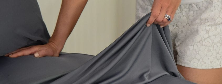 woman holding corner of gray cooling top sheet