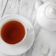 red tea in white cup next to white tea kettle on wood table