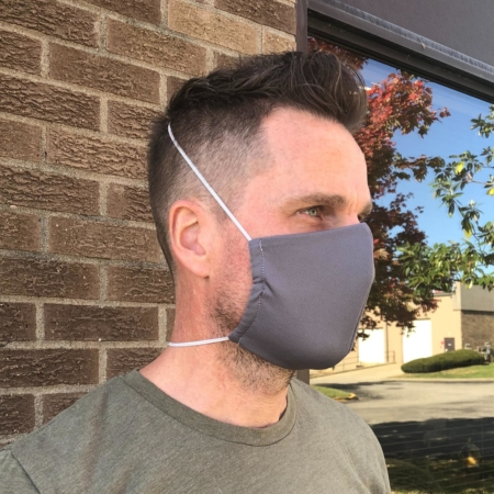 man wearing a gray wicked sheetsbreathable face mask with thin elastic