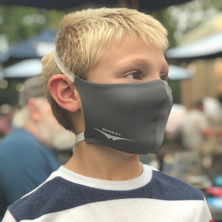 little blonde boy wearing a wicked sheets gray days of the week face mask labeled monday